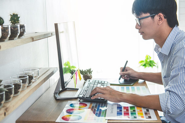 Graphic designer working on a desktop computer with a stylus.