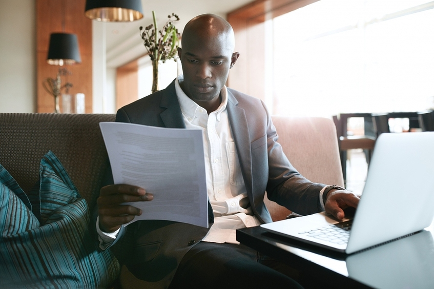 Man in a business suit working at a laptop and reading a document.