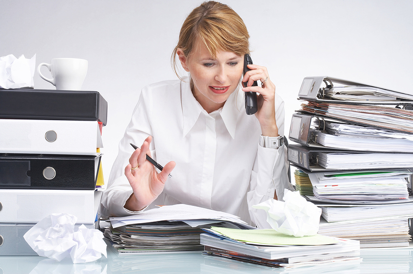 Woman talking on the phone surrounded by towers of binders.