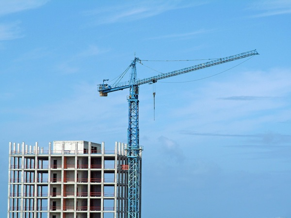 Crane on top of a tall building under construction.