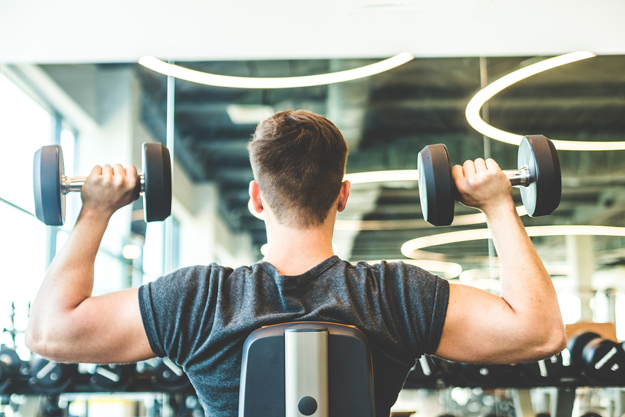 Man lifting dumbbells in a gym.