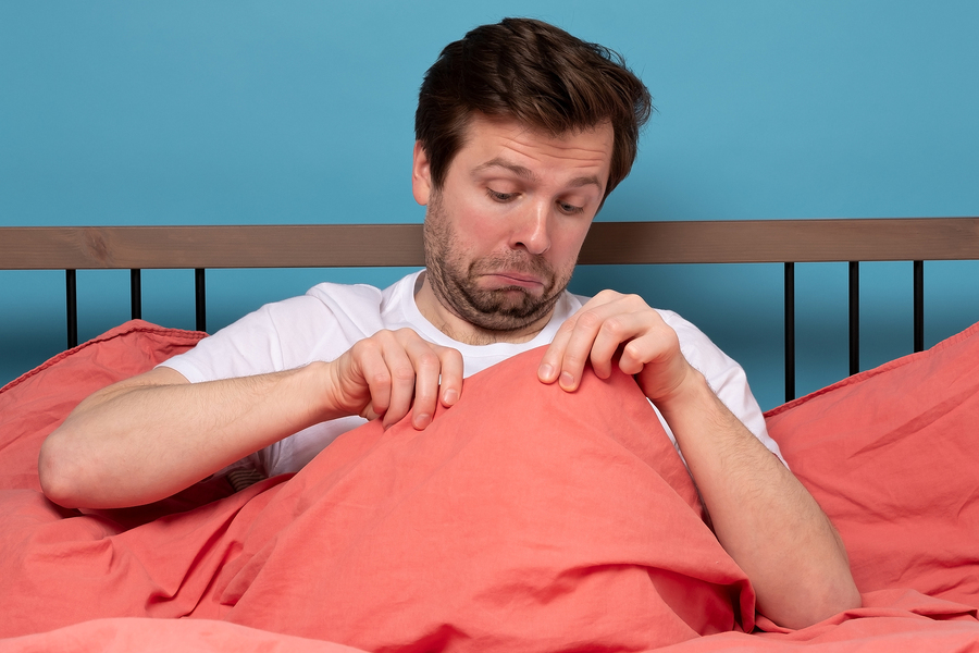 Man peaking under his own blanket.