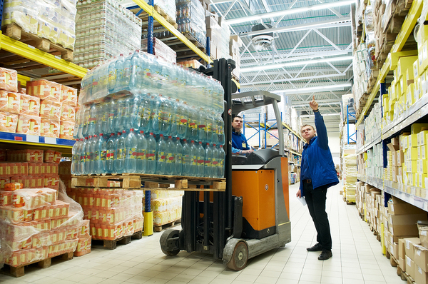 Warehouse workers moving pallets of food with a lift.