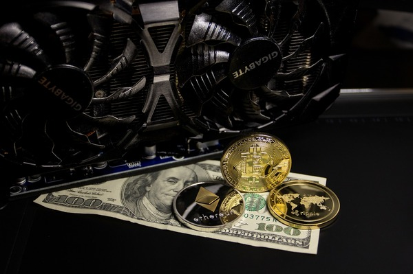 Computer fan with gold bitcoin coins and a 100 dollar bill.