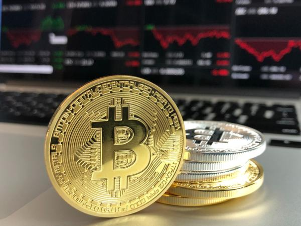 Gold and silver bitcoin coins with charts and graphs.