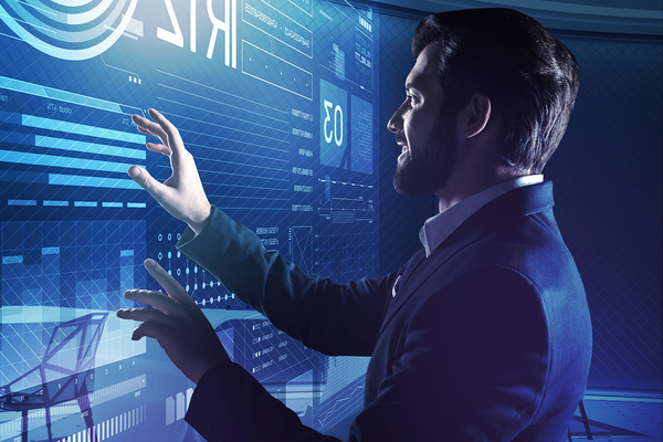 Man in a business suit looking at a large screen with data.