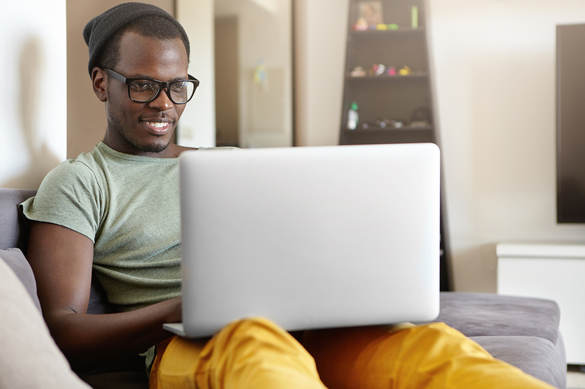 Man sitting on a couch using his laptop.