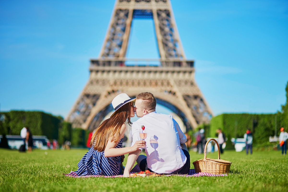 Couple kissing in front of the Eiffel Tower.