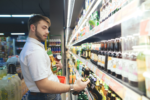 Man shopping in a grocery store buying beer.
