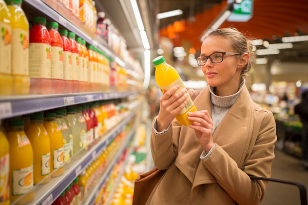 Woman shopping in a grocery store holding a bottle of orange juice.