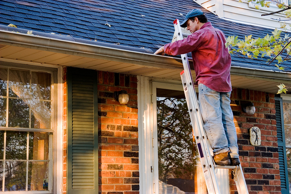 Man on a ladder cleaning out gutters.
