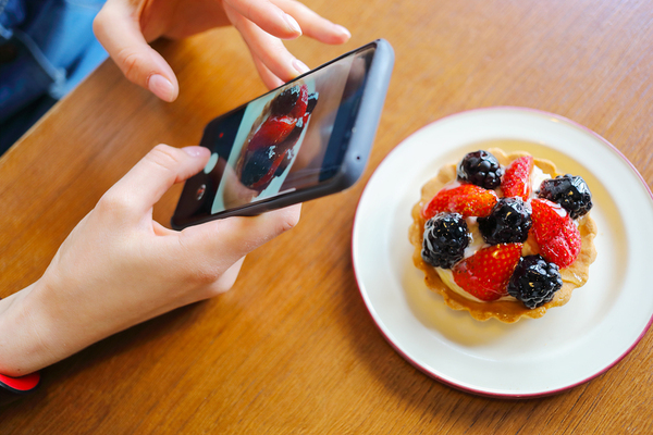 Person taking a picture of a fruit tart.