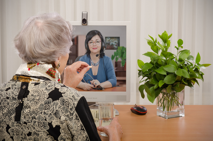 Elderly woman taking medication while consulting a medical professional in a video conference.