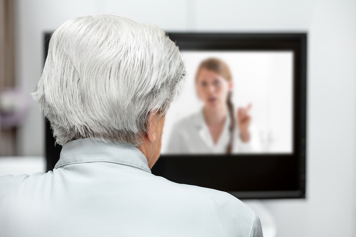 Elderly person having a video conference with a doctor.