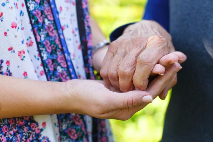 Caregiver holding the hand of an elderly person.
