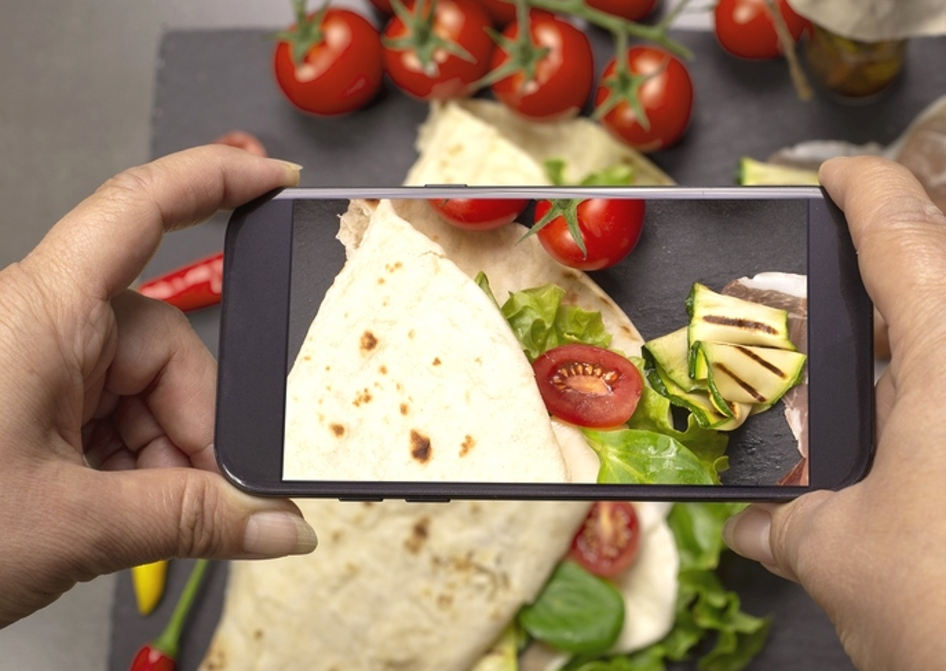 Person taking a photo of a salad wrap on a plate.
