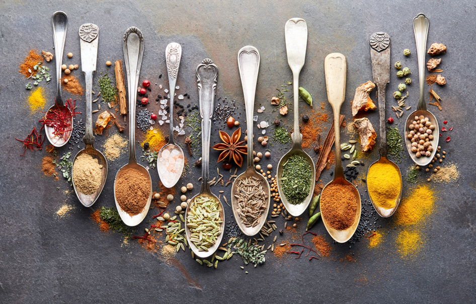 Silver spoons filled with herbs and spices.