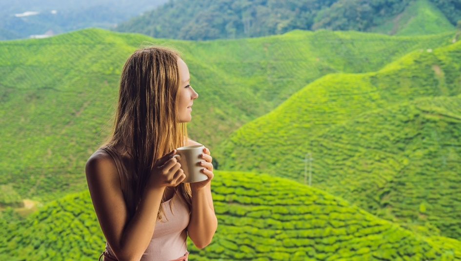 Woman drinking a cup of coffee with green hills in the background.