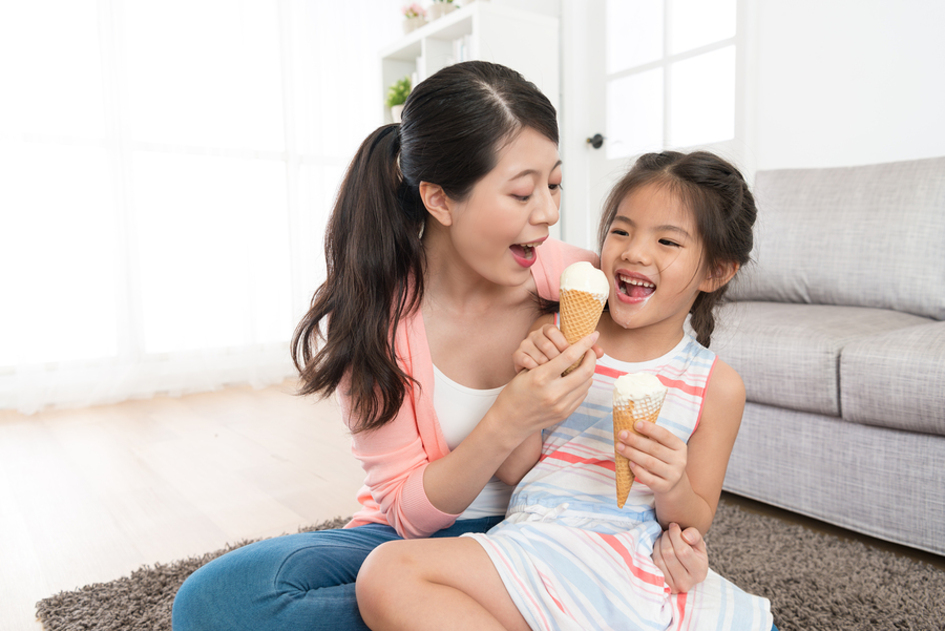 Woman giving her daughter an ice cream cone.