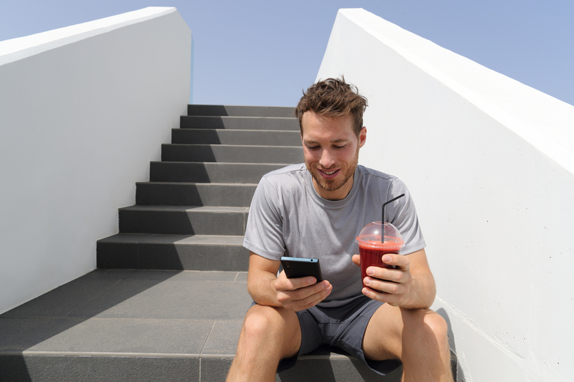 Man sitting on steps with his phone and a drink.