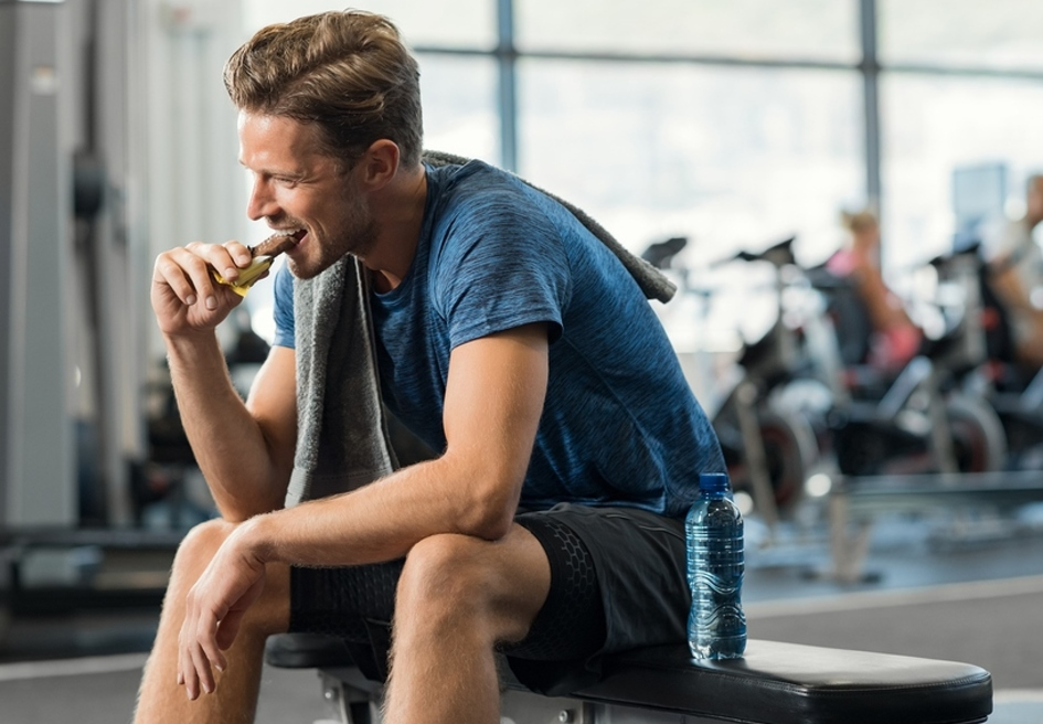 Man at a gym eating a bar.