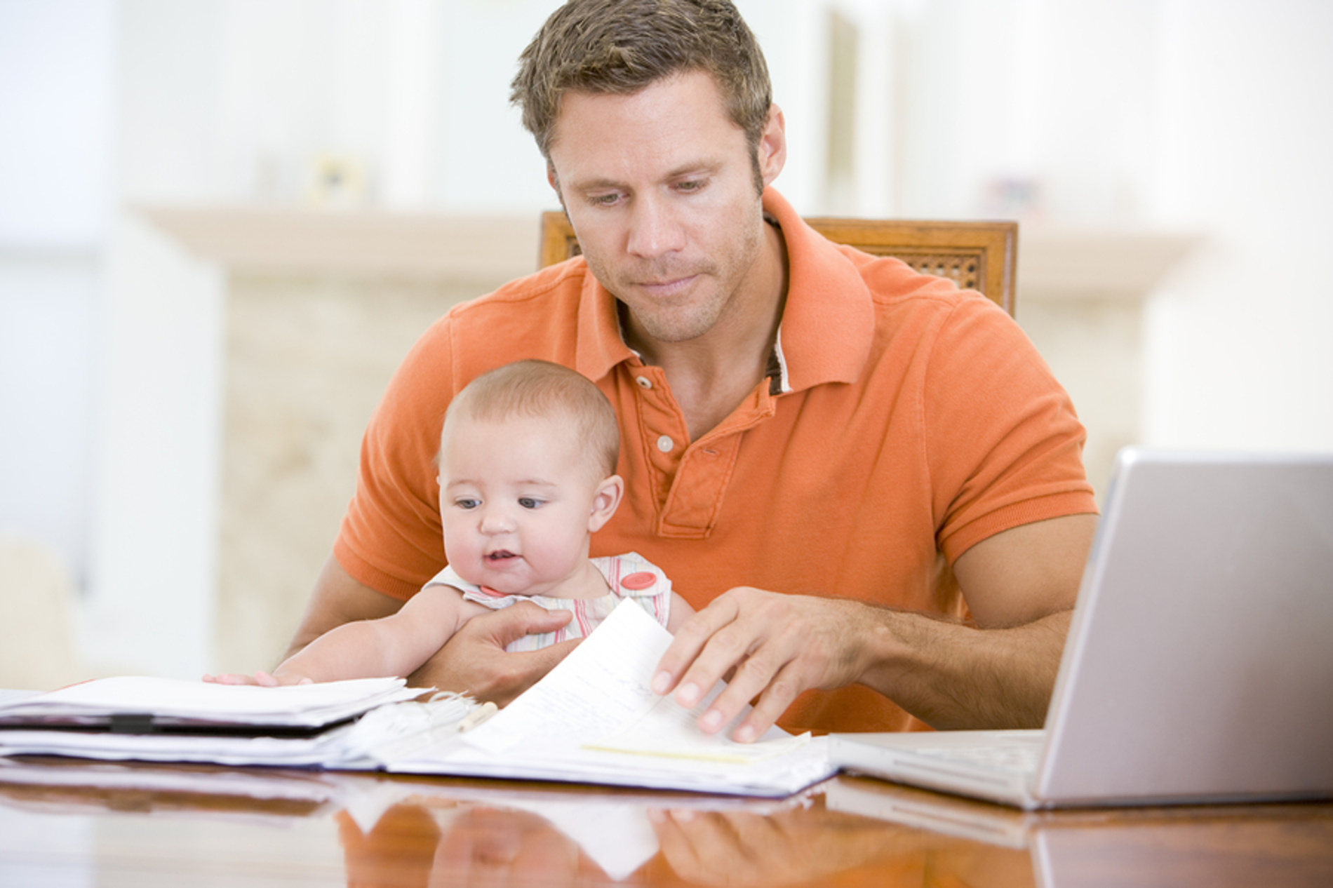 Dad with his baby looking at paperwork at a desk.