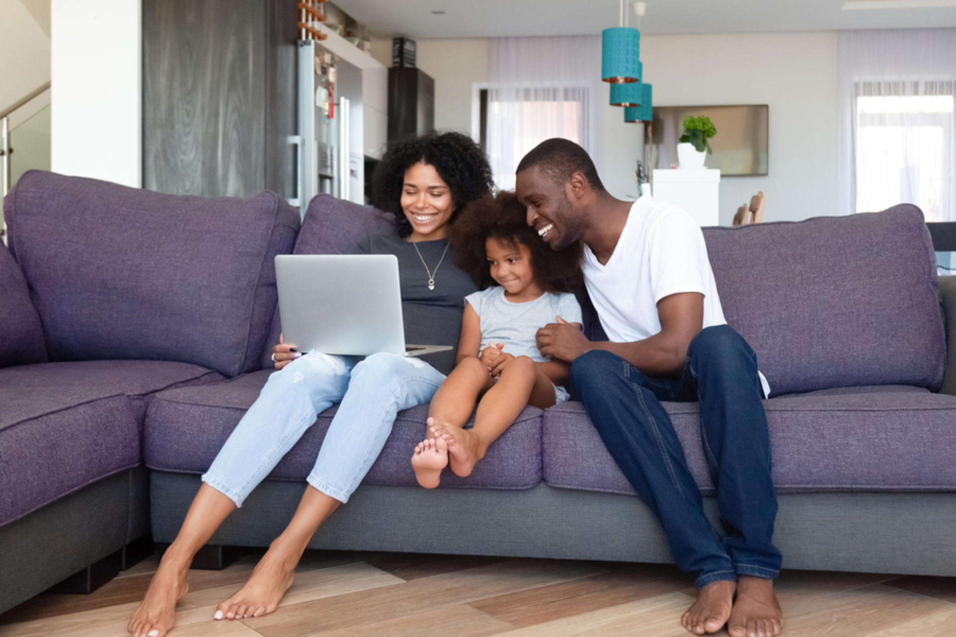 Happy family sitting on a couch looking at a laptop together.