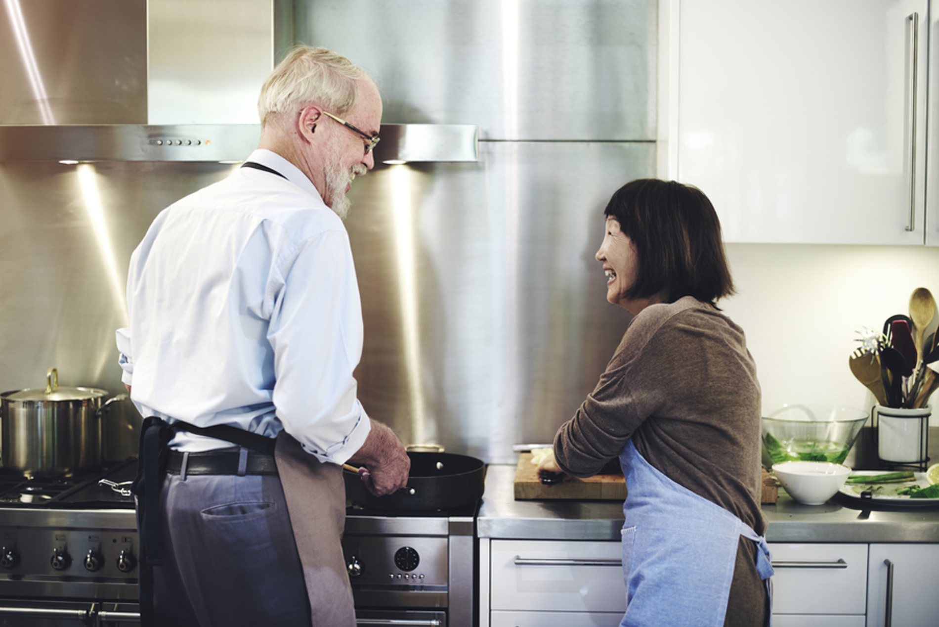 Two people cooking in a kitchen.