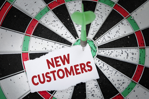 White, black green and red dart board with a note New Customers on it.