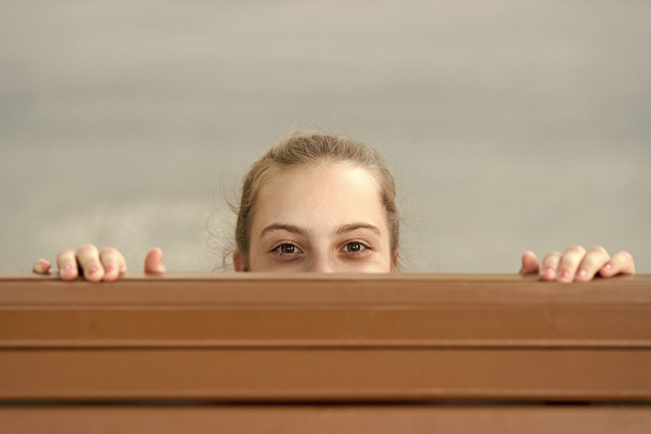 Woman peaking over the top of a hood.