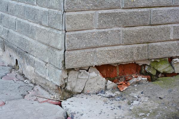 Corner of a brick building with broken bricks at the bottom.