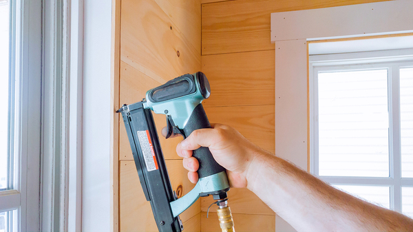 Person using a nail gun to install windows.