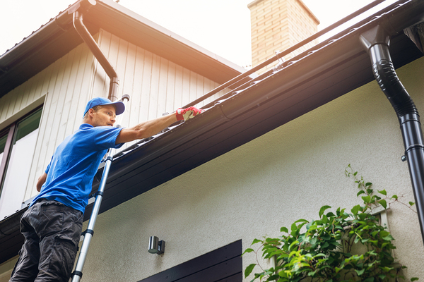 Man installing gutters on a house.