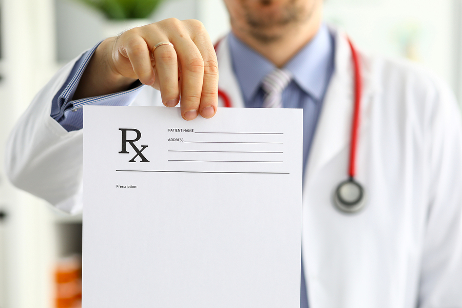 Medical doctor holding a prescription document.