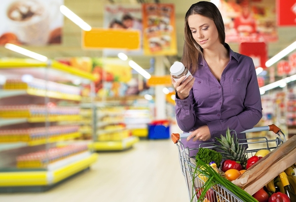 Woman shopping in a grocery store looking at a product label.