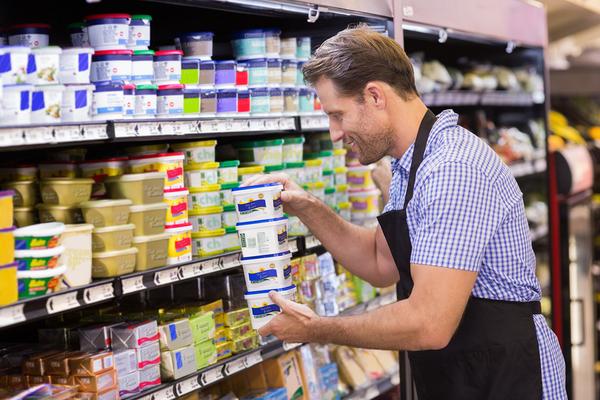 Man filling grocery isle.