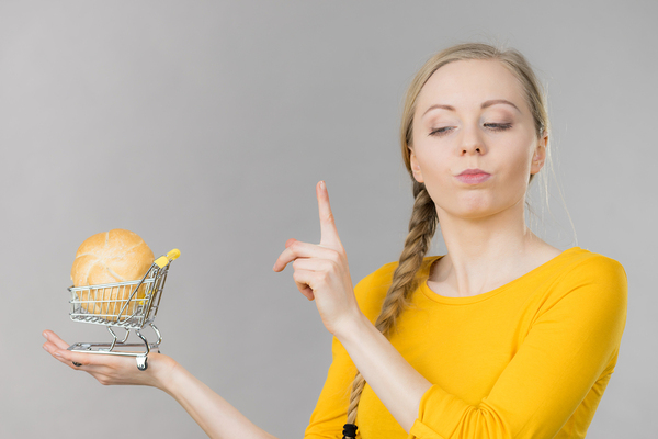 Woman holding a miniature shopping cart looking cautious.