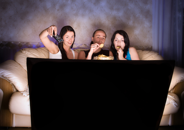 Three young adults sitting on a couch watching TV eating snacks.