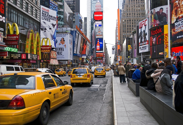 City street filled with yellow taxis and neon signs.