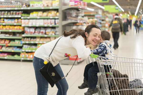 Mom shopping in grocery store with child in cart.