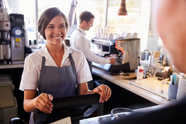Person ordering an item from a coffee shop from a woman in a blue apron smiling.