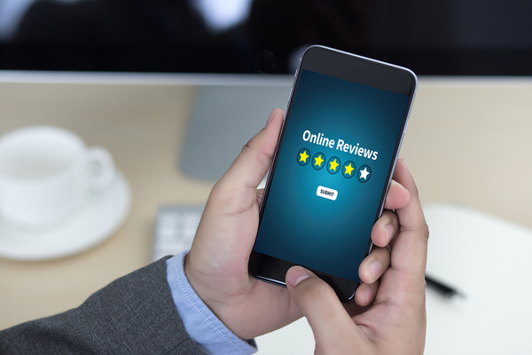 Person holding a mobile phone with online reviews displayed on the screen.