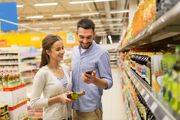 Man and woman shopping in a grocery store using a mobile app.