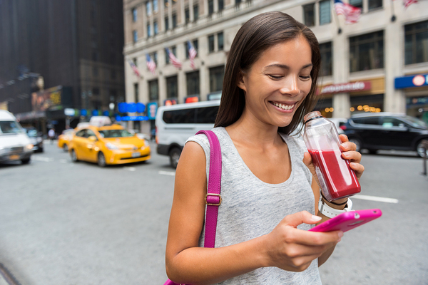 Woman smiling while using her mobile phone.