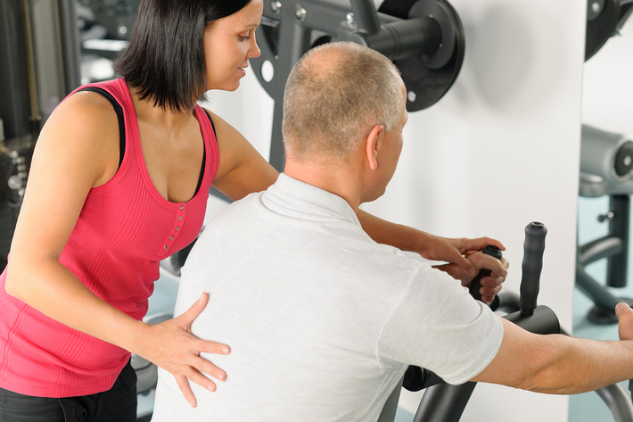 Personal trainer helping a man on equipment.