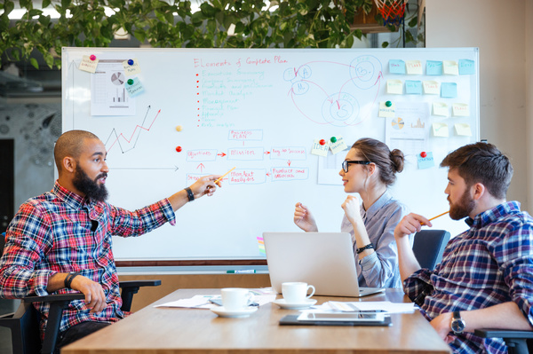 Three colleagues discussing information on a whiteboard.