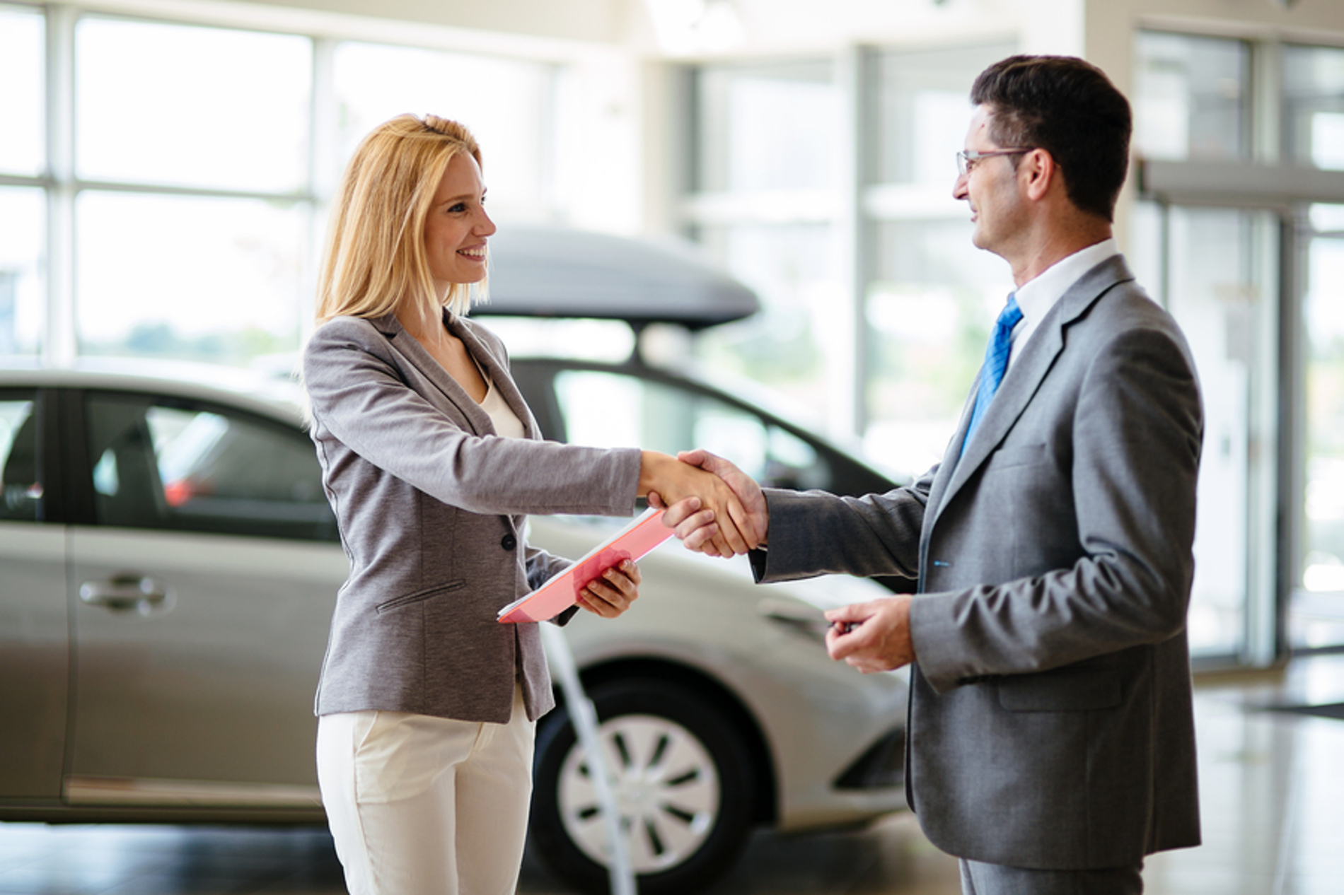 Woman shaking hands with a car salesman.