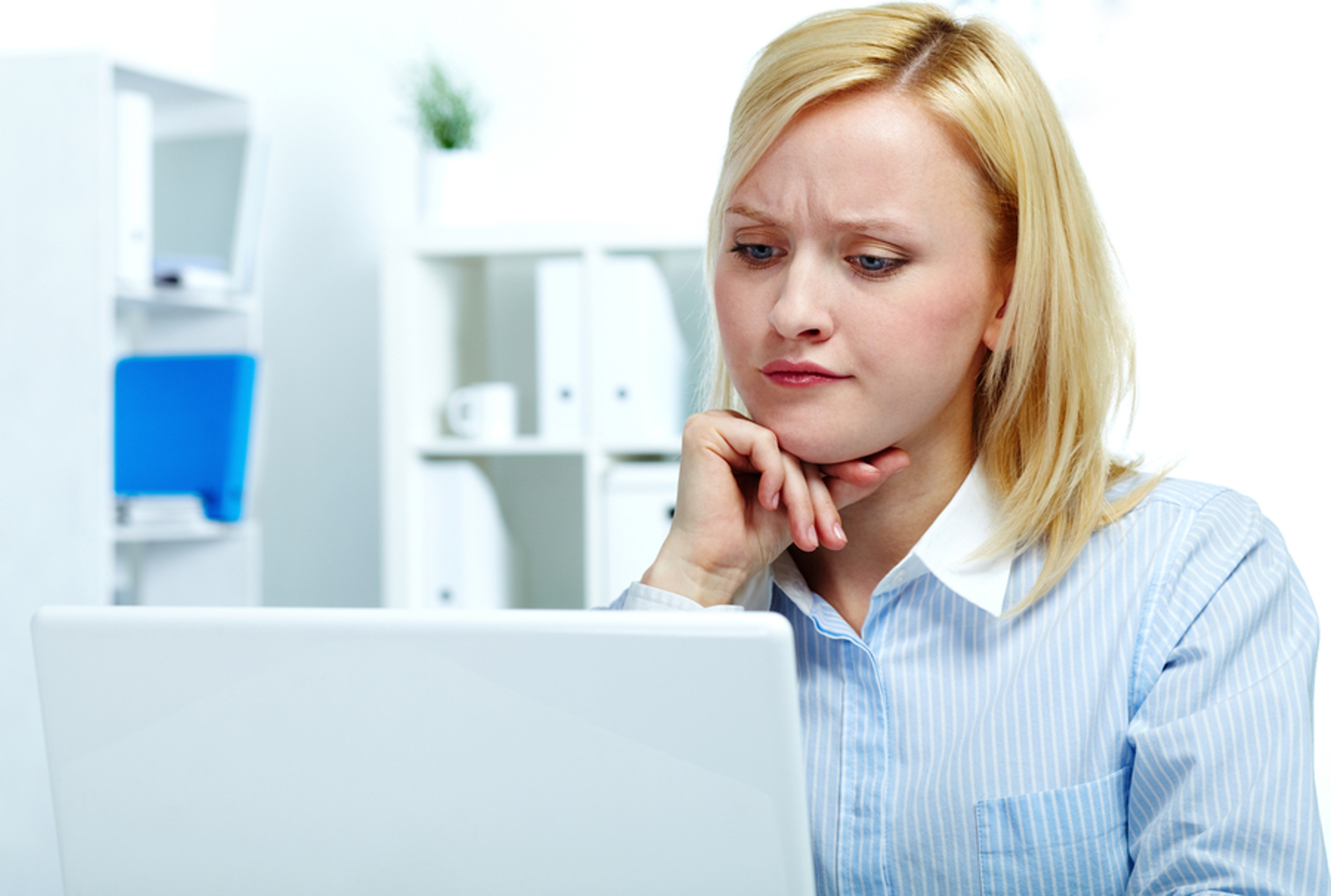 Woman sitting in front of her computer looking confused.