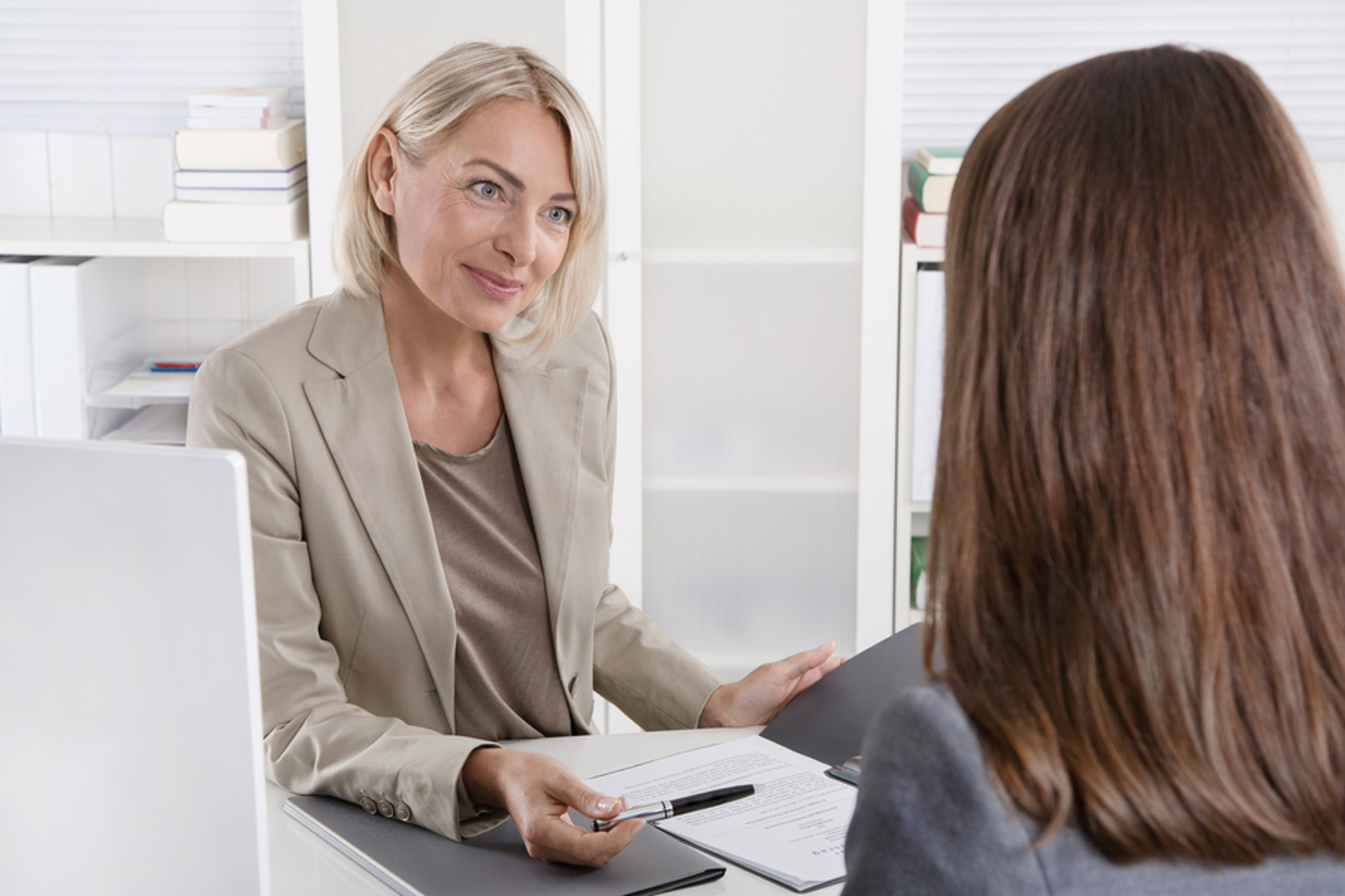 Woman financial services professional discussing paperwork with a customer.