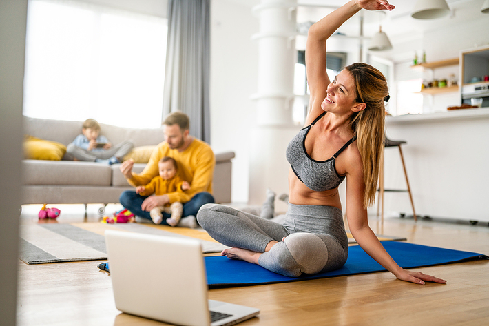 Woman sitting on the floor stretching in front of her laptop.